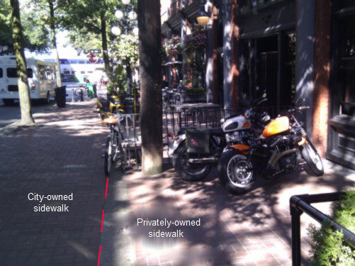 Free parking on private property beside restaurant in Gastown.  Note the line separating the private sidewalk where you can legally park, and the city sidewalk where Vancouver will ticket your bike.